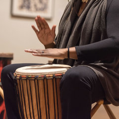 Nicole Williams, from Rhythm To You, teaches the technique of hand drumming in a unifying drum circle with members of the community at the Snite Museum.