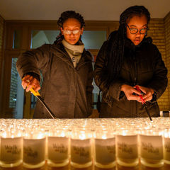 Students Ashley Lizana and Mackenzie Isaac light the candles before the candlelight prayer service in honor of Rev. Martin Luther King Jr.